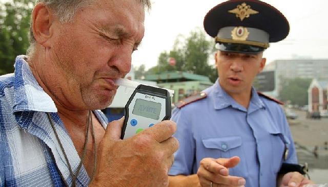 Сотрудник ГИБДД проверяет шофера алкотестером